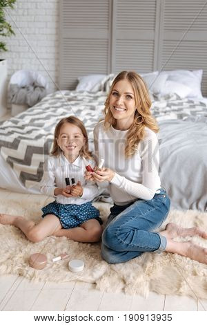First makeup lessons. Joyful little girl and her gorgeous young mother sitting on the carpet in the bedroom and holding some cosmetics in their hands
