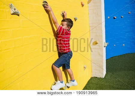 Portrait of smiling boy climbing yellow wall at playground in school
