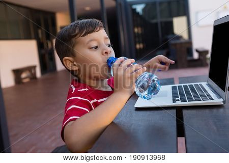 Boy drinking water while using laptop at table in school