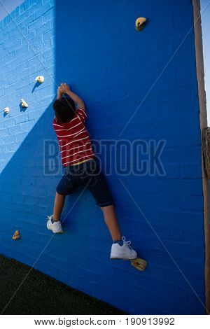 Rear view of boy climbing blue wall at playground in school