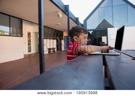 Side view of boy using digital laptop while sitting at table in school