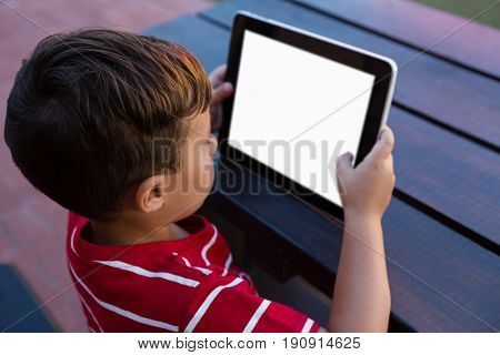 High angle view of boy using digital tablet while sitting at table in school