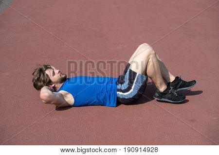 abdominal exercises. athletic bearded man or sexy handsome guy with muscular body doing exercises for abdominal on stadium sunny outdoor in blue sportswear summer activity and sport healthy lifestyle and workout