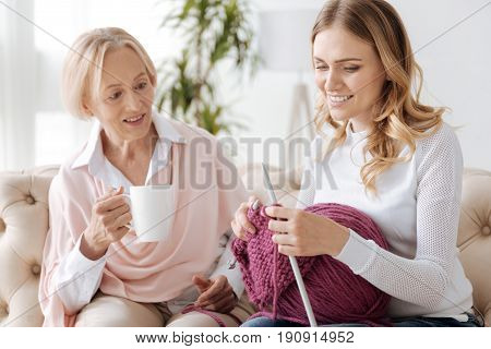 Beautiful golden-haired woman knitting a scarf with purple threads and holding a big ball of threads on her lap, while her elegant mother holding a mug of tea and looking at her knitwork