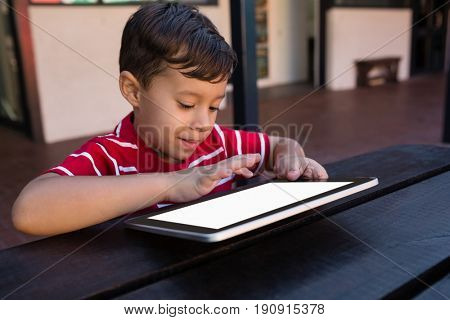 Close up of smiling boy using digital tablet while sitting at table in school