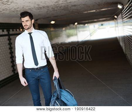 Young man walking in underpass.