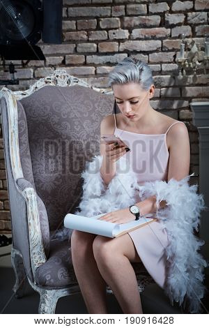 Retro styled actress having break, using mobilephone, reading script.