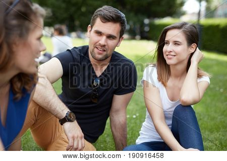 Young friends sitting in park, outdoors, talking.