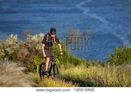 Attractive cyclist riding the mountain bicyclist on the summer trail above the river. Young sportsman in the black sportwear, with helmet and with backpack. Travel in the countryside. Concept of the healthy lifestyle.