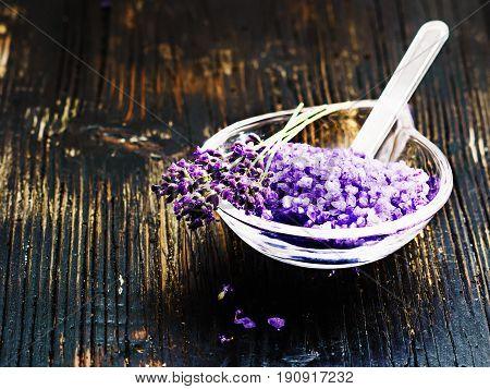 ingredients for lavender spa, flower and salt  on black wooden background.