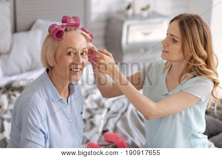 Celebration preparations. Elegant senior woman wearing pink hair rollers and receiving help with extra pieces from her beautiful young daughter.