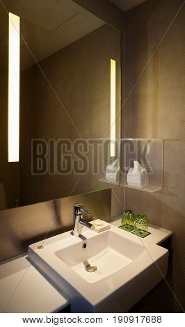 Water faucet with square white basin in a modern lavatory with illuminated mirror and brown tiles.