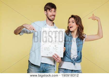 Picture of happy brother and sister showing nameplate over yellow background. Looking camera.
