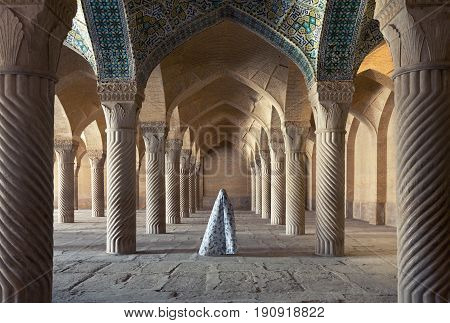 SHIRAZ, IRAN - SEPTEMBER 16, 2014: Woman in veil standing between columns of Shabestan of Vakil Mosque. This religious place was built between 1751 and 1773, during reign of Zand dynasty over Iran.