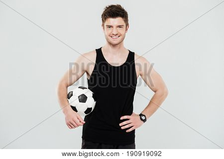Image of happy young sportsman with foot ball standing isolated over white background. Looking at camera.