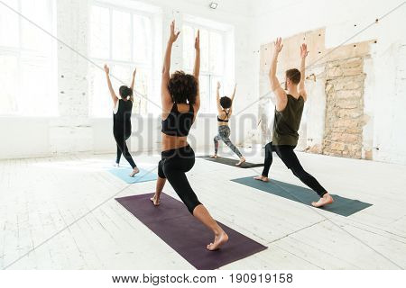 Back view of group of young healthy people wearing tracksuits doing yoga in gym