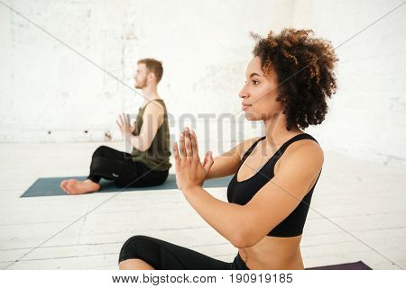 Side view of young african woman doing yoga in gym