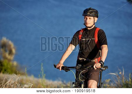 Attractive cyclist standing with mountain bicyclist on the summer trail above the river. Young sportsman in the black sportwear, with helmet and with backpack. Travel in the countryside. Concept of the healthy lifestyle.