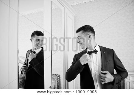 Handsome Groom Dressing Up And Getting Ready For His Wedding In The Room.
