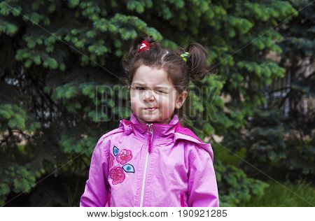 The girl with pigtails closes one eye looks into the camera.