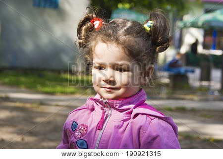 The little girl with pigtails looks away. Close-up.