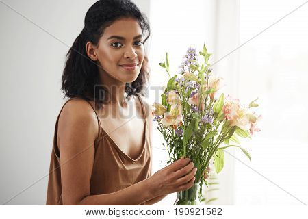 Beautiful african female florist smiling looking at camera making bouquet of flowers. White wall background. Copy space.