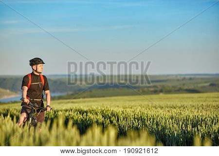 Young attractive cyclist standing up with mountain bicyclist in the summer green field. Sportsman dressed in the black sportwear, with helmet and backpack. Beautiful landscape with blue sky. Concept of the healthy and active lifestyle.