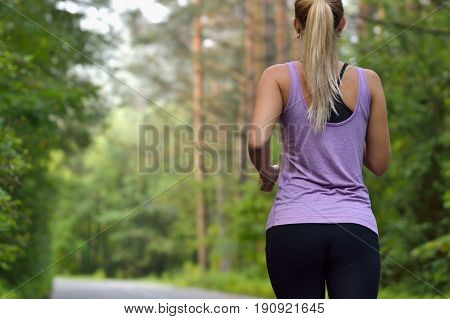 Young athletic sporty girl with long hair training in green forest during summer or autumn season. Back view with copy space
