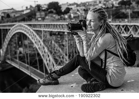 Young pretty woman with photocamera sitting on the view point in front of the Douro river and the Dom luis I bridge in Porto, Portugal. Black-and-white photo.
