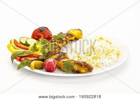 Marinated and grilled chicken kebab with rice herbs and salad placed on a plain plate. Low angle studio shot over white table top. Fusion food concept for poultry dish served in Persian restaurants.