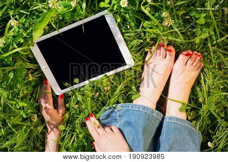 Woman with tablet pc outdoors body parts. Hands and legs with bright red polished nails copy space on the black screen clipping path for screen included