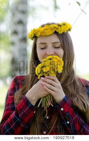 Girl with a bouquet of dandelions and a wreath on her head enjoying the smell
