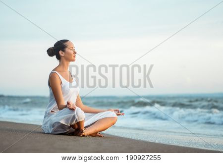 Young woman in lotus pose outdoors