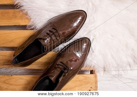 Brown patent leather shoes on a pallet white fur. Fashionable concept