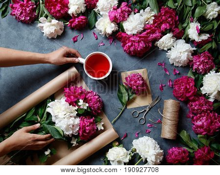 Tools and accessories florists need for making up a bouquet out of peonies: kraft paper, scissors, string, an envelope on the table. Florist at work. View from above. Flat lay. Karkade tea.
