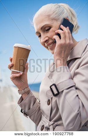 smiling grey haired woman talking on smartphone and holding coffee cup outdoors