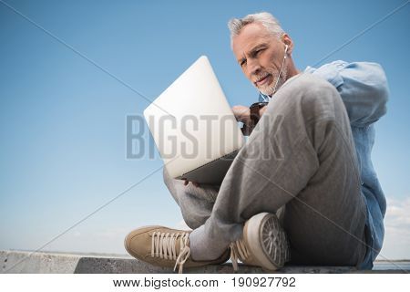 Pensive Elderly Man Working On Laptop And Listening Music In Earpods Outdoors