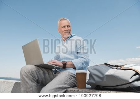 Smiling Senior Man Using Laptop And Listening Music In Earpods At Quay