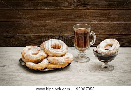 Donuts With Icing Sugar, A Mug Of Tea And Currant Jam On A Wooden Background
