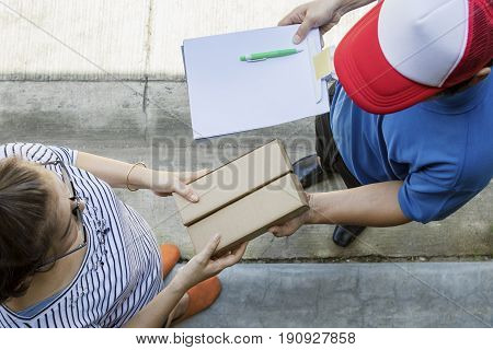 woman accepting on line shopping product from home delivery man top view scene