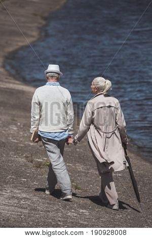 Casual Elderly Couple Walking On River Shore At Daytime