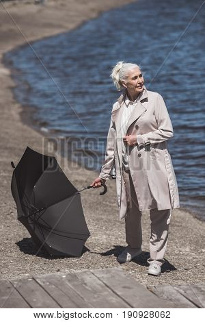 Casual Senior Woman Posing With Umbrella On Riverside At Daytime