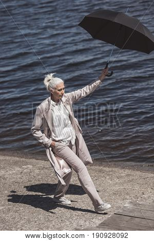Casual Grey Haired Woman Walking With Umbrella On River Shore At Daytime