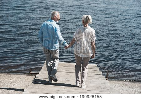 Casual Elderly Couple Holding Hands And Walking On Riverside At Daytime