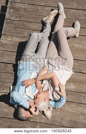 Above View Of Senior Couple Hugging While Lying On Wooden Pavement