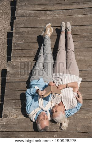 Above View Of Senior Couple Reading Book While Lying On Wooden Pavement