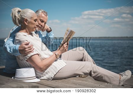 elderly couple reading book while sitting on the quay at daytime