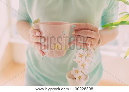 Female hands with a beautiful manicure hold a pink cup and a branch with white flowers