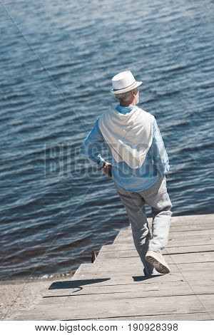 Back View Of Casual Senior Man Walking By Pavement On The Riverside At Daytime