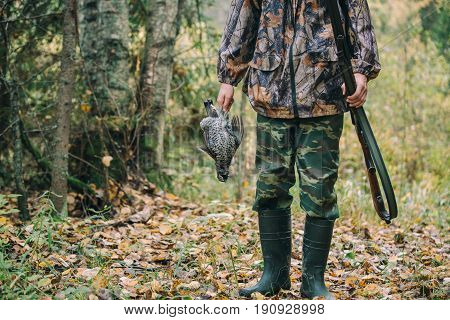 Hunter with hunting rifle and wildfowlin autumn forest